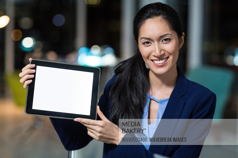Portrait of businesswoman showing digital tablet in the office