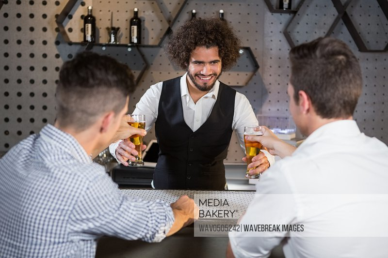 Bartender serving beer to customers at bar counter in bar