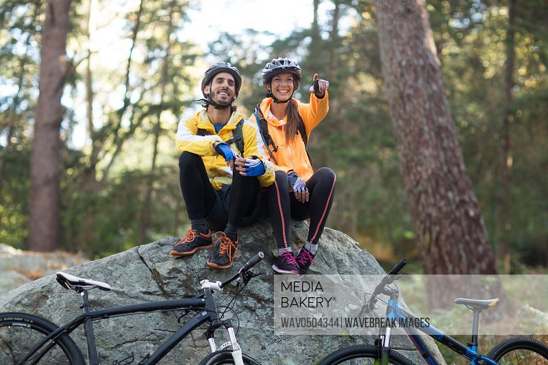 Biker couple sitting on rock and pointing in distance at countryside forest