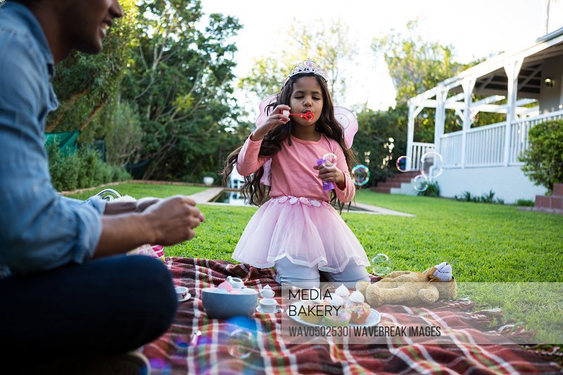 Girl blowing soap bubbles in the garden