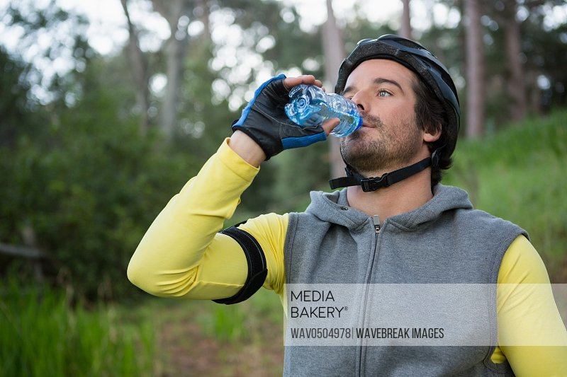Mountain biker drinking water in the forest