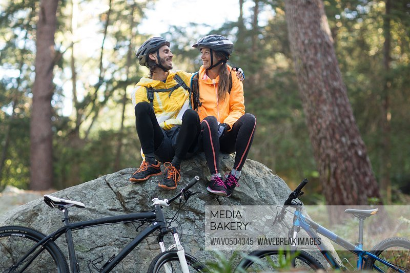 Biker couple sitting on rock and interacting with each other at countryside forest