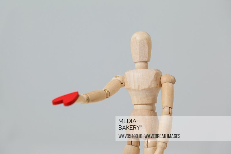 Wooden figurine standing and giving a red heart against grey background