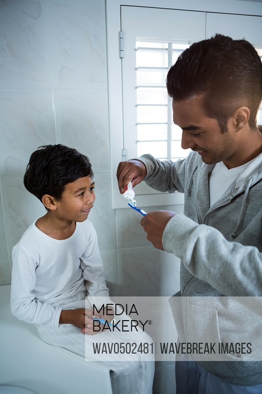 Father and son brushing teeth in the bathroom at home