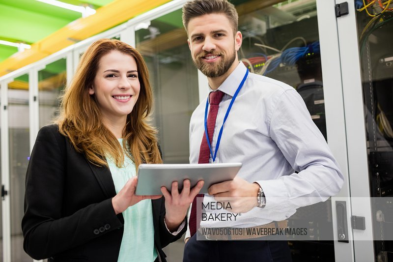 Portrait of smiling technicians standing in server room with digital tablet