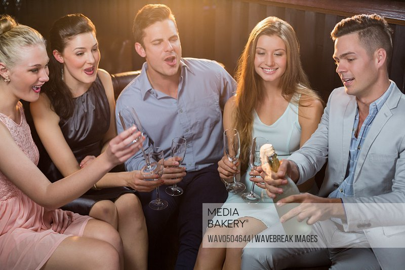 Man popping a champagne bottle while friends watching him at bar