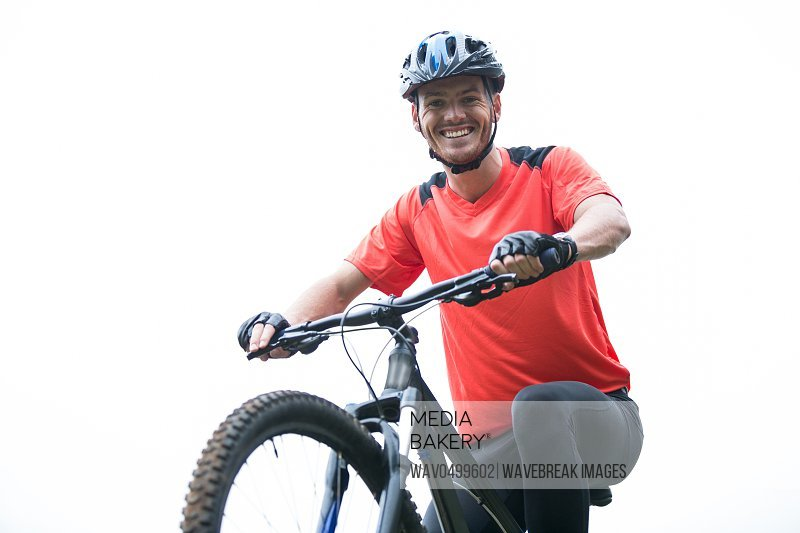 Portrait of male cyclist cycling in countryside on sunny day
