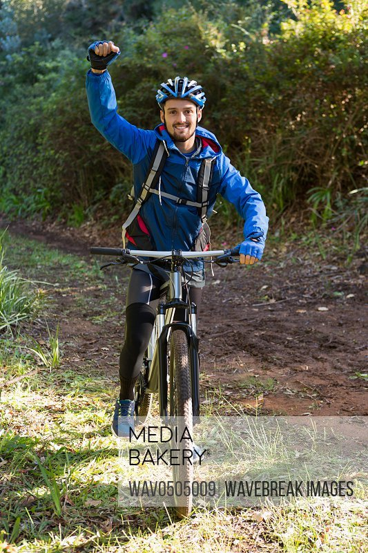 Portrait of excited male mountain biker in the forest on a sunny day