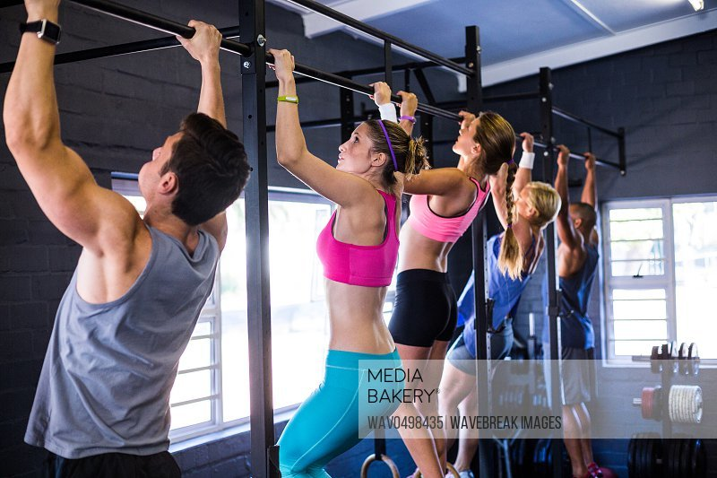 People doing chin-ups while exercising in gym