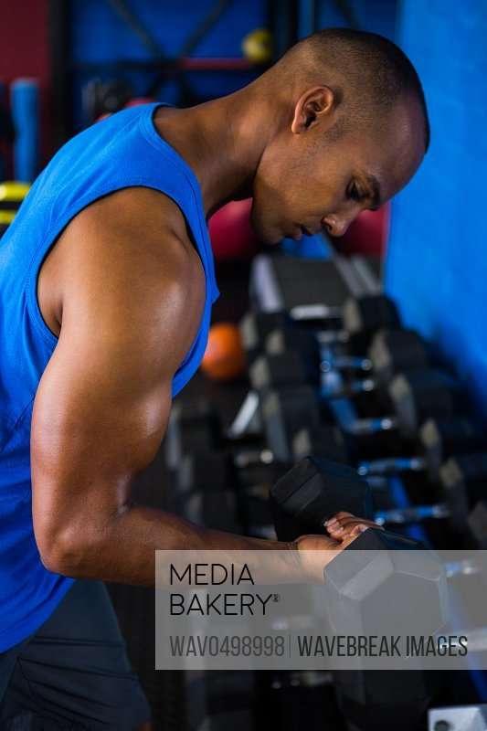 Side view of male athlete exercising with dumbbell in fitness studio