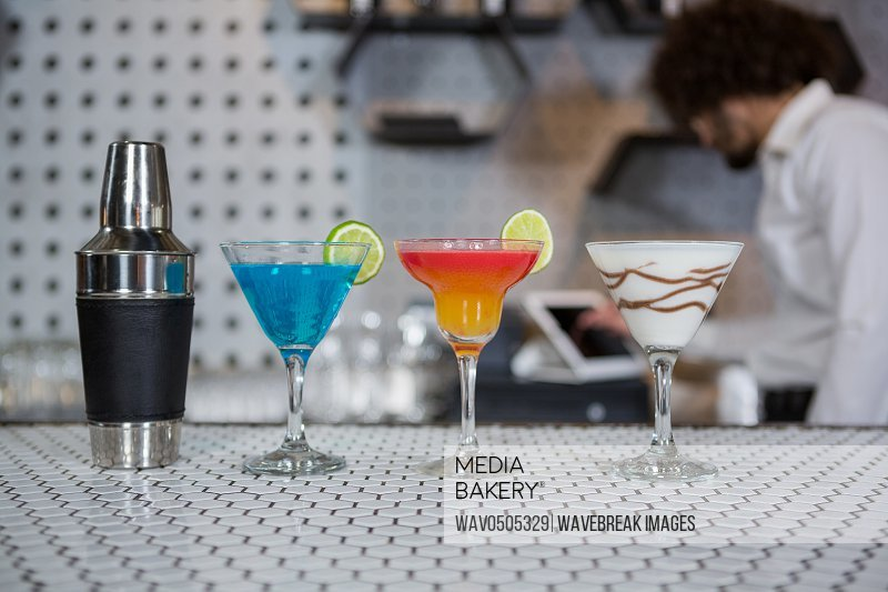 Various cocktails drinks and cocktail shaker on a bar counter in bar