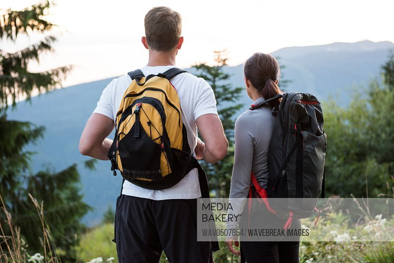 Couple standing and looking at a view in countryside forest