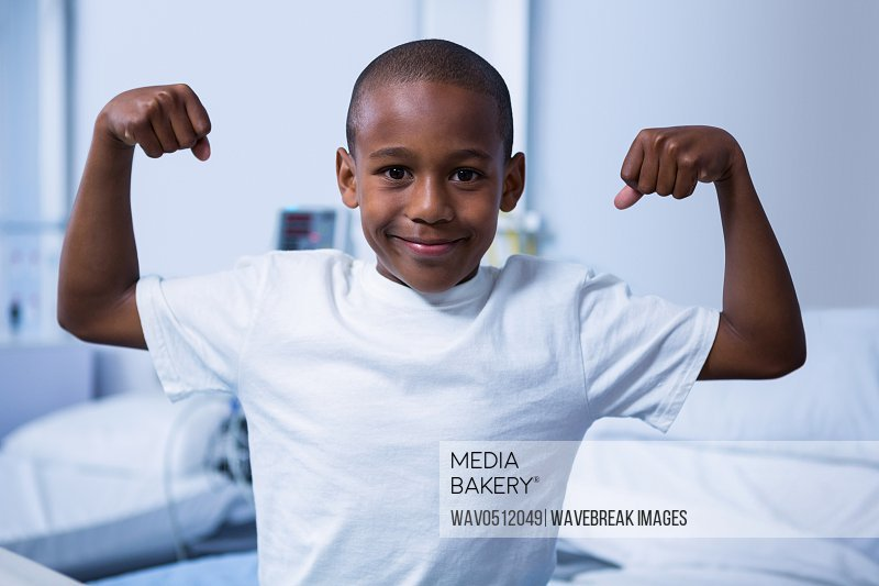 Portrait of boy flexing his muscles in ward at hospital