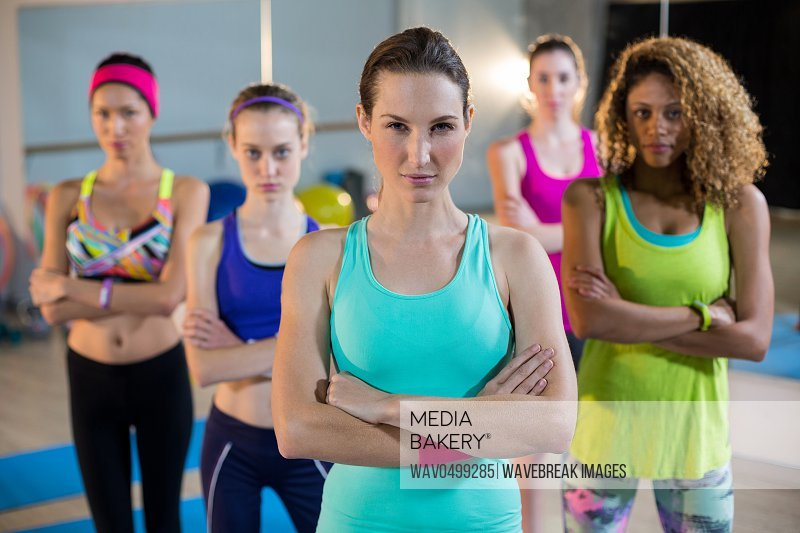 Group of women standing with arms crossed in gym