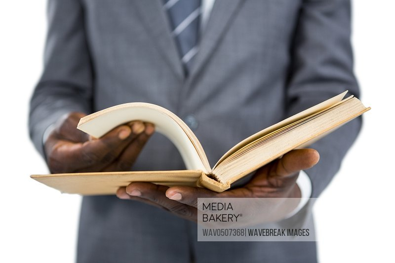 Mid section of businessman flipping the pages of a book against white background