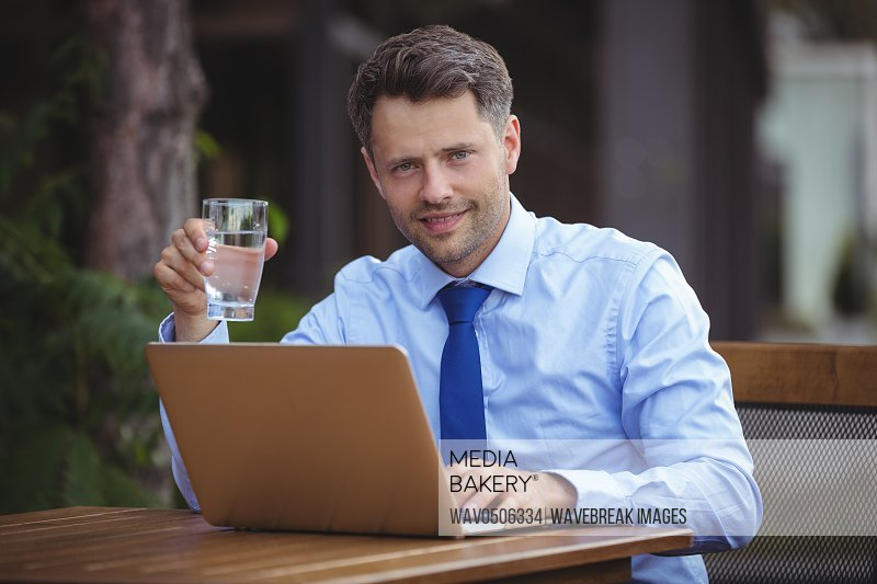 Handsome businessman having drink while using laptop at outdoor cafA?