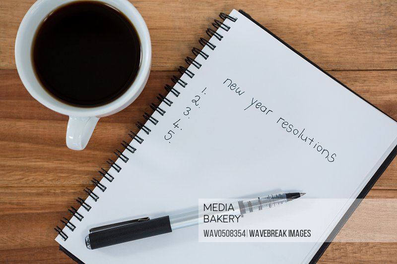 Close-up of coffee cup with diary and pen on table in office