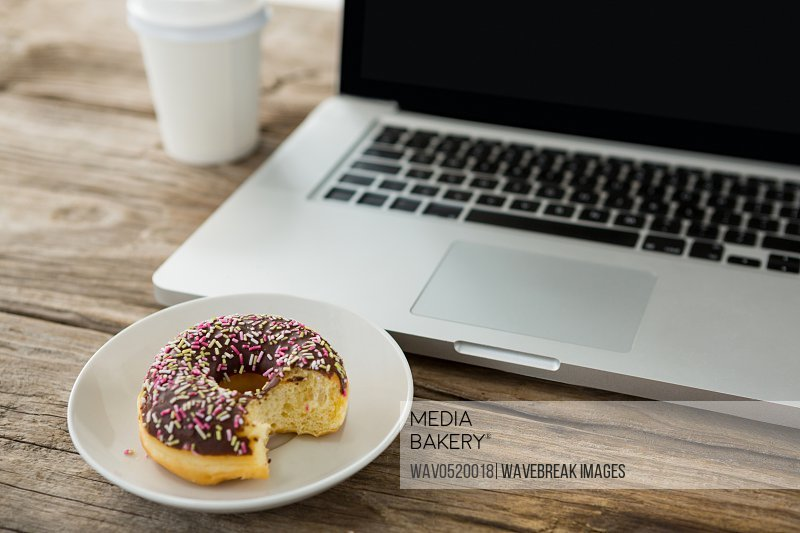Laptop and doughnut on wooden table