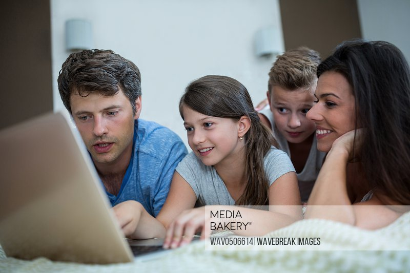 Happy family using laptop in bedroom at home