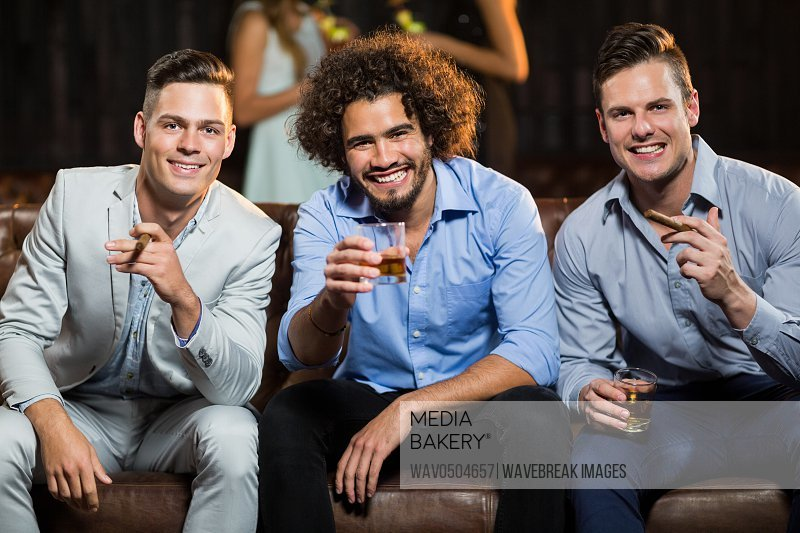 Portrait of three happy friends having cigar and whisky in bar