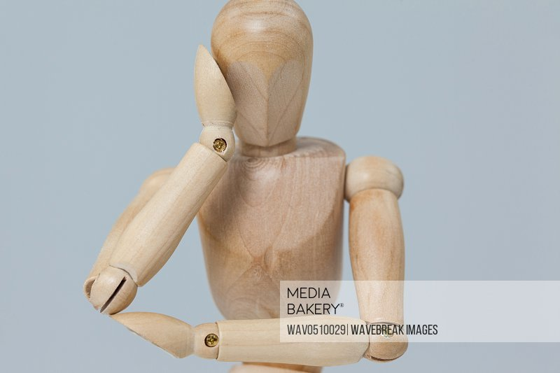 Thoughtful wooden figurine pretending to lean against grey background
