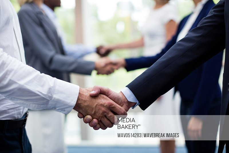 Mid section of business executives shaking hands with each other