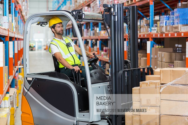 Male worker using forklift in warehouse