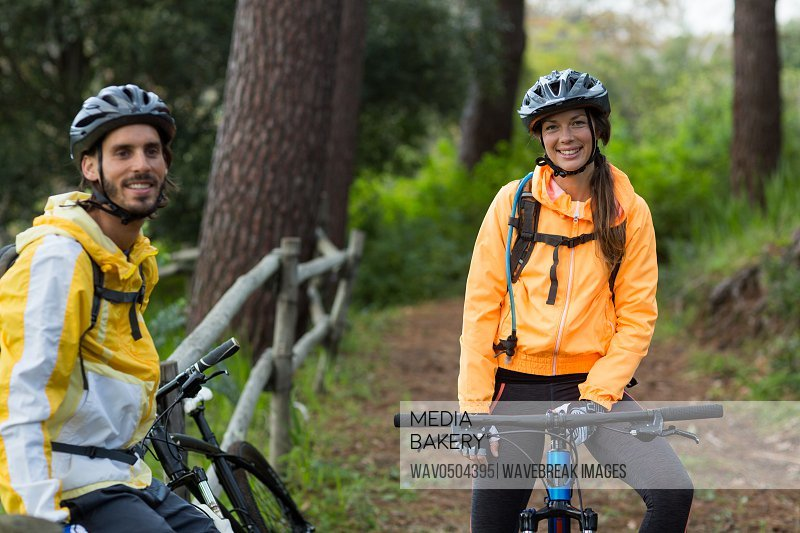 Portrait of biker couple with mountain bike in countryside forest