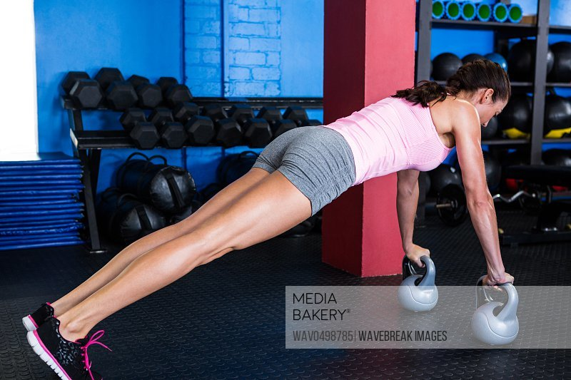 Side view of female athlete doing push-ups with kettlebell in gym