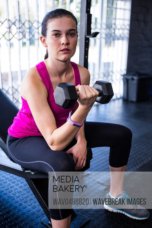 Portrait of sporty female athlete lifting dumbbell in gym
