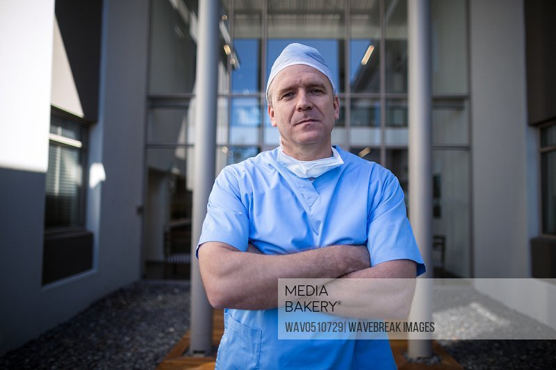 Portrait of male surgeon standing with arms crossed in hospital corridor