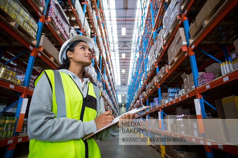 Female warehouse worker looking at packages in warehouse