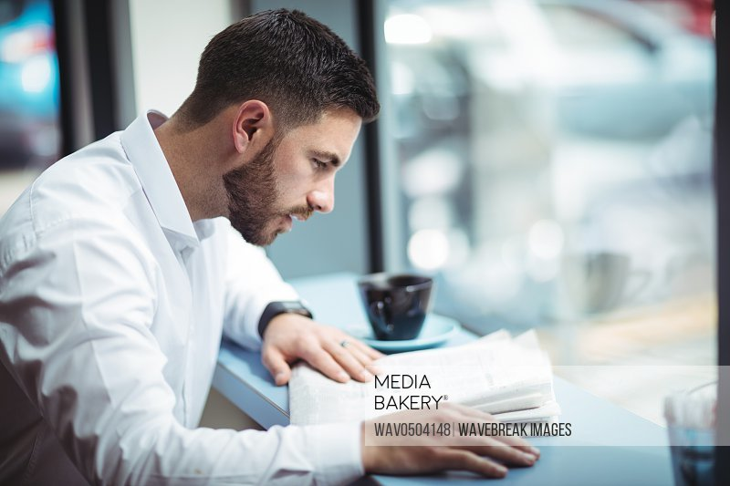 Businessman sitting at table and reading newspaper in office