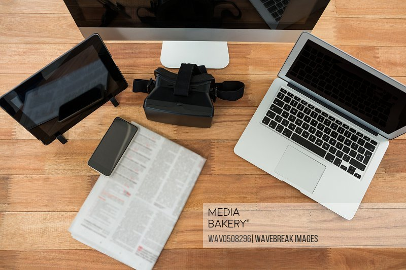 Computer laptop digital tablet mobile phone virtual headset and newspaper on wooden table