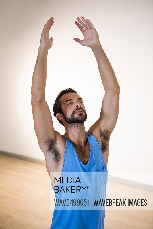 Man performing stretching exercise in fitness studio