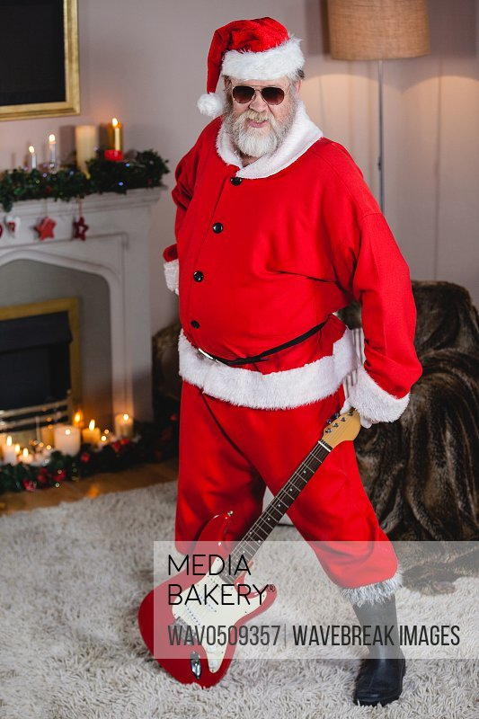 Smiling santa claus standing with a guitar