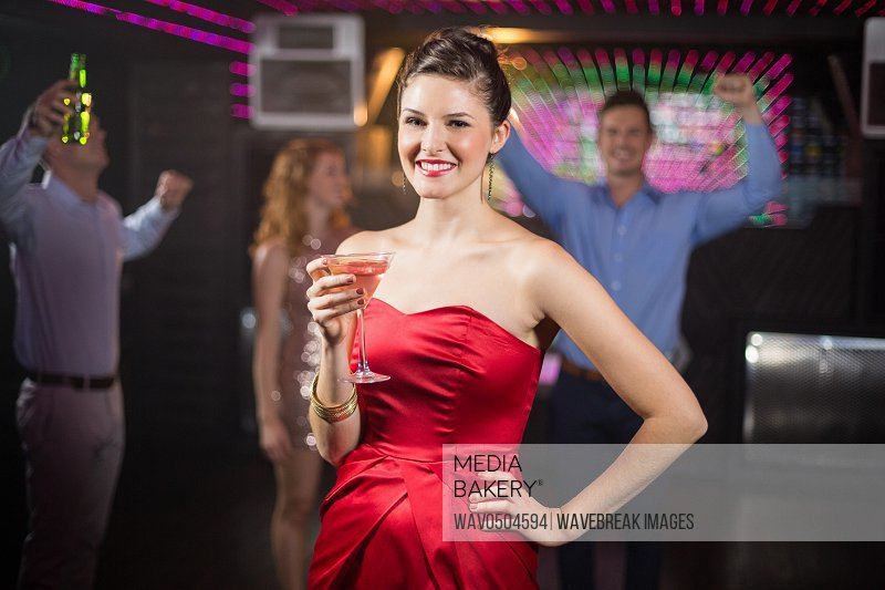 Portrait of young woman holding a glass of cocktail in bar