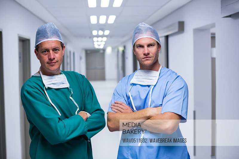 Portrait of surgeon and nurse standing with arms crossed in corridor