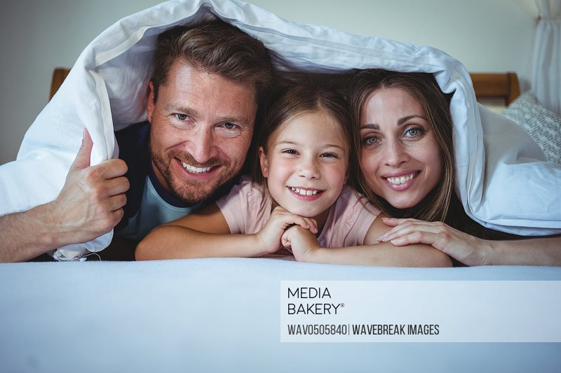 Happy family lying under a blanket on bed at home