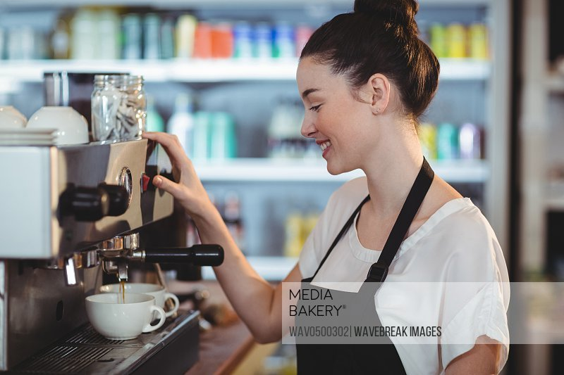 Smiling waitress making cup of coffee at cafe
