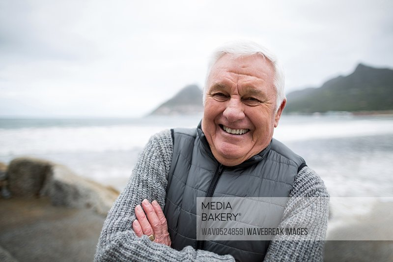 Portrait of senior man standing with arms crossed on the beach