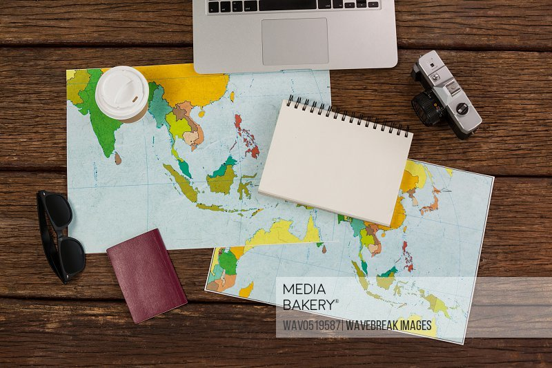 Laptop camera notepad maps passport and wayfarer
