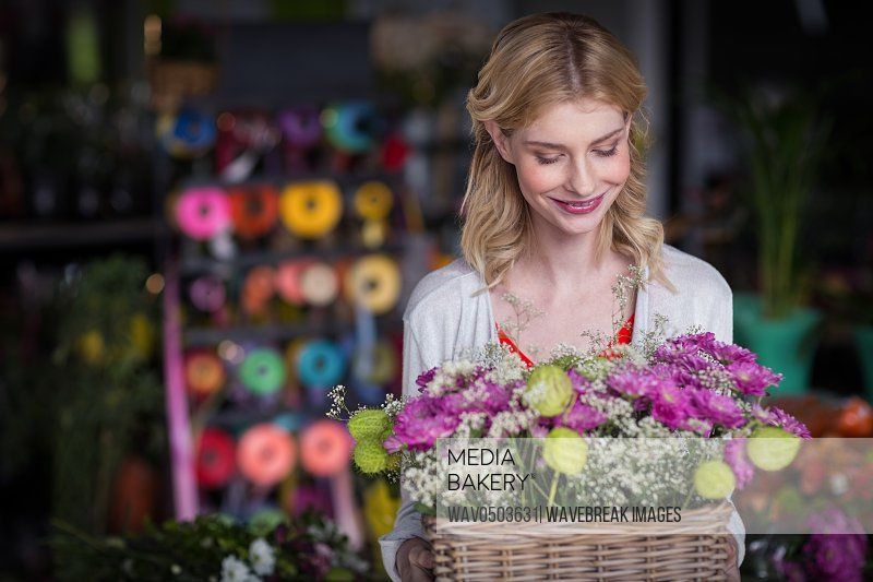 Happy female florist holding basket of flowers in the shop