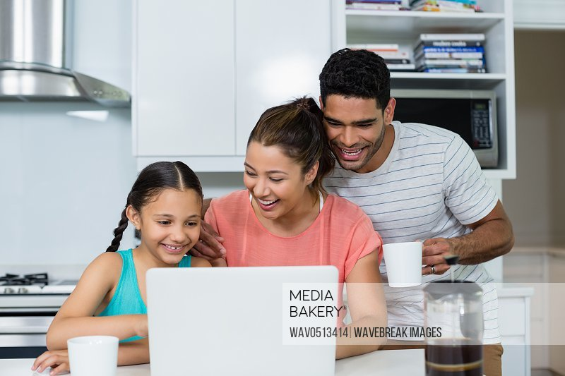 Parents and daughter using laptop in kitchen at home
