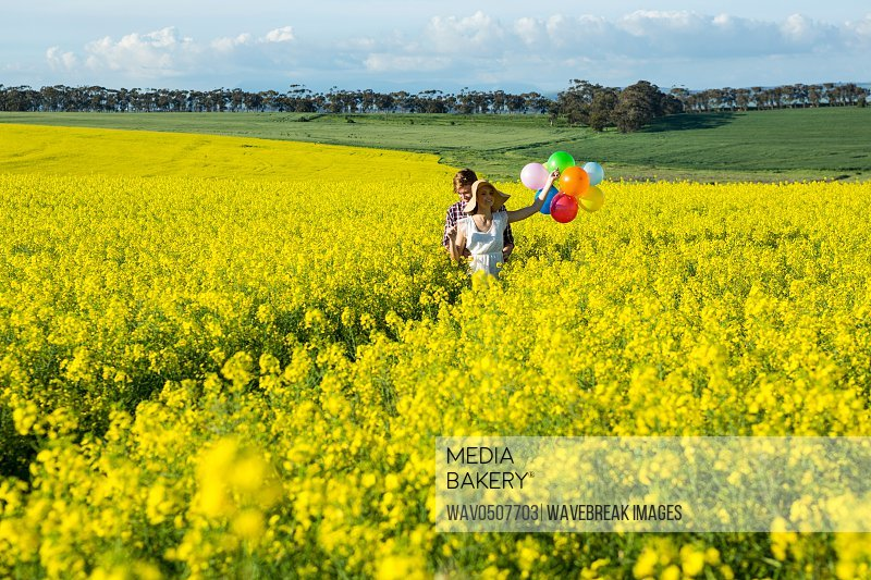 Couple holding colorful balloons in mustard field on a sunny day