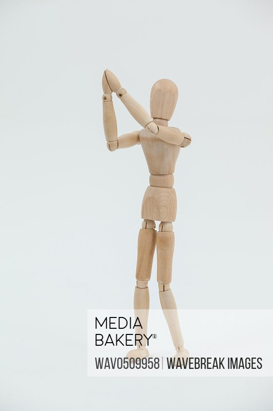 Wooden figurine standing with both the hands joined against white background