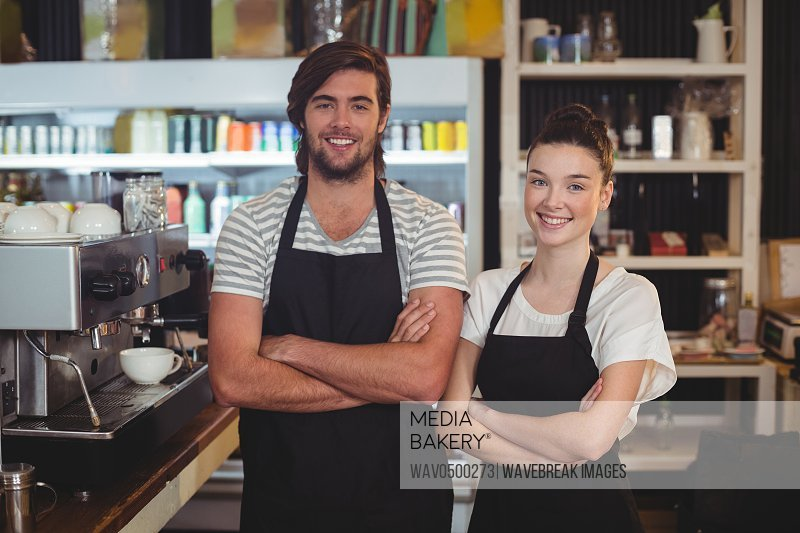 Portrait of waiter and waitress standing with arms crossed in cafe
