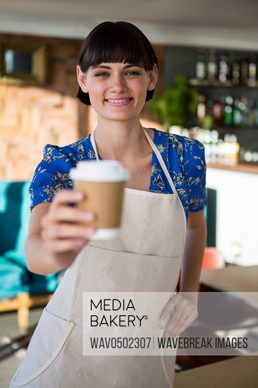 Portrait of smiling waitress offering a cup of coffee