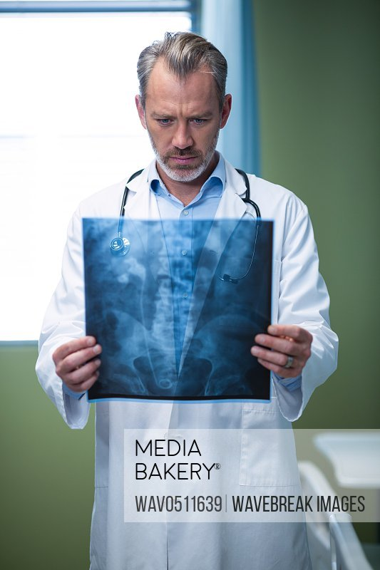 Doctor analyzing patient x-ray in ward of hospital