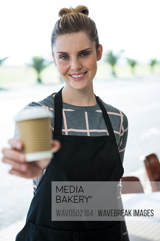 Portrait of smiling waitress offering coffee in cafA?